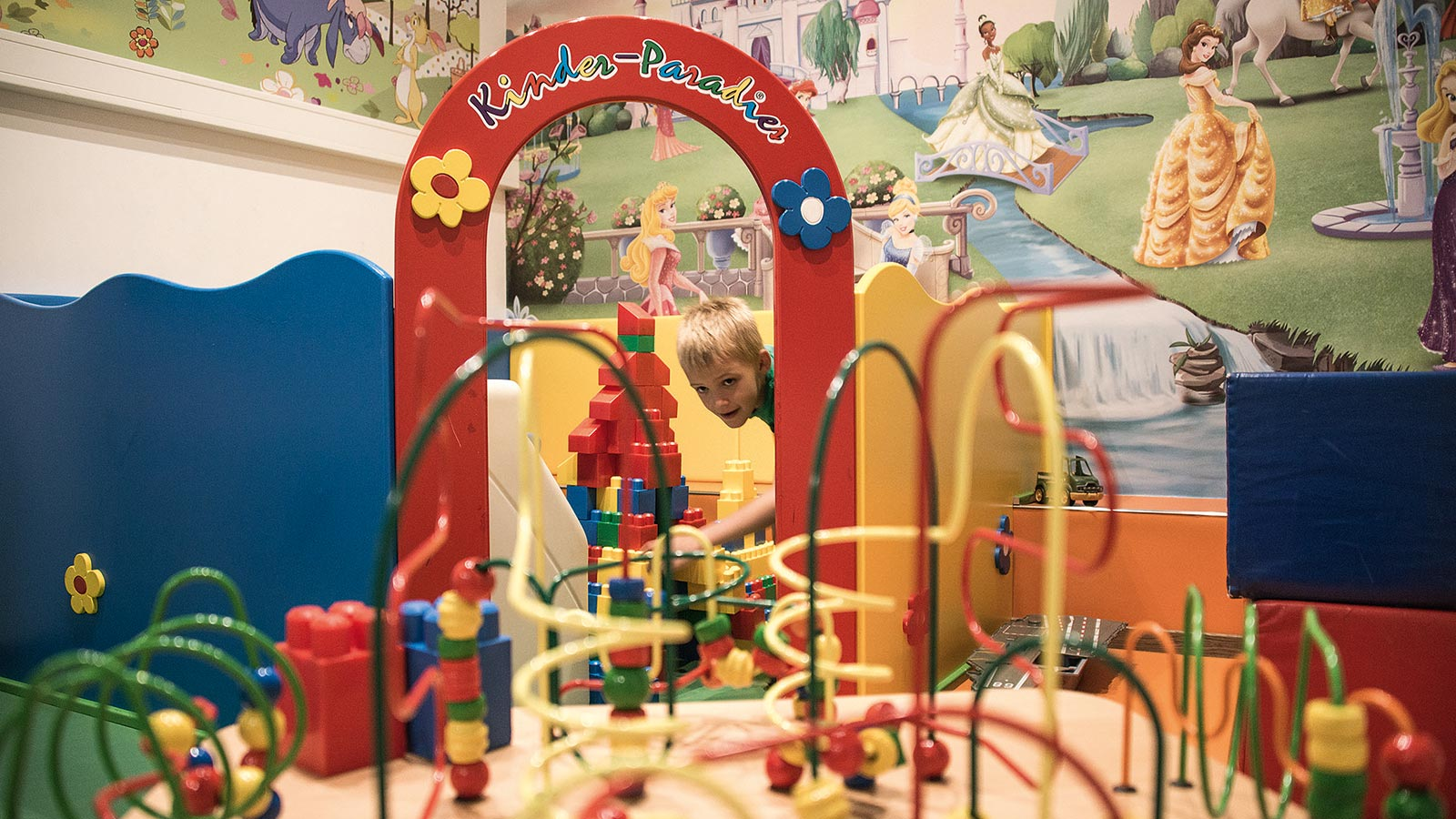 a blonde child playing in Parkhotel Holzerhofs playroom